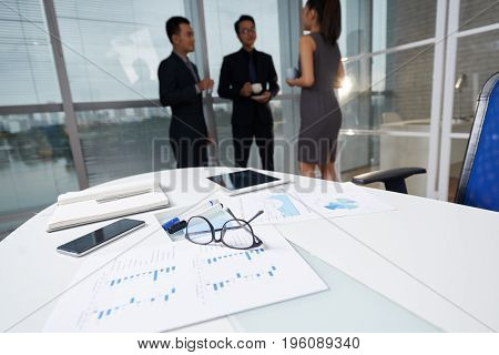 Table with business documents in meeting room, entrepreneurs are talking in the background