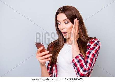 Oh No! Really?! Young Astonished Brunette Lady Standing On The Pure Light Blue Background, Reading N
