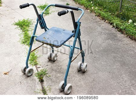 horizontal image of an old worn out and broken seniors wheeled walker.
