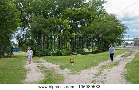 horizontal image of two gravel trails meeting up in the fore front with a