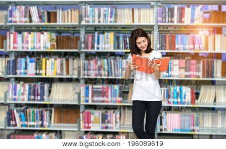 Young Student Asian Women Teenager with school folders reading book at library university campus college knowledge center