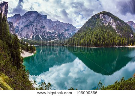 South Tyrol, Italy. Magnificent lake Lago di Braies. Green water reflects the surrounding mountains and forest. The concept of walking and eco-tourism