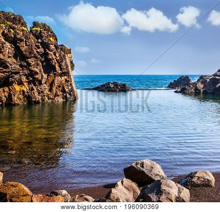 The stony shore of the Atlantic ocean. Small bay with smooth water. Volcanic island of Madeira. The concept of exotic and ecological tourism