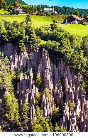 Renon's earth pillars at sunrise. The charming small village in the Dolomites in Tyrol, Italy. The concept of ecological tourism