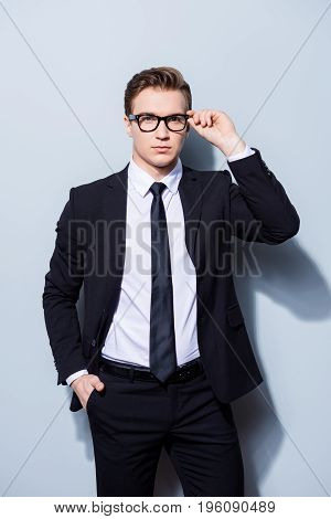 Successful Young Handsome Businessman Banker In A Suit Is Fixing His Glasses, He Stands On Pure Ligh