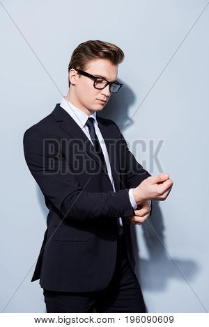 Young Handsome Businessman Lawyer In A Suit Is Fixing His Cuffl Inks, He Stands On Pure Light Backgr