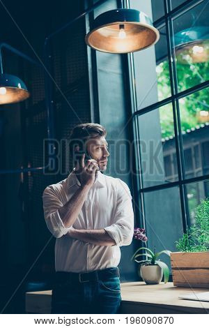 Young Well Dressed Entrepreneur Is Talking On His Mobile Phone At The Modern Office, Looks At The Wi