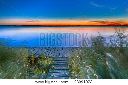 Long Exposure Image Of Blue And Orange Sunset Over A Pier On The Shore Of A Lake