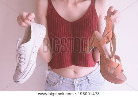 Close up of female hands holding high heels shoes and casual sports shoes.