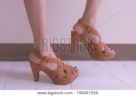 Close up of female legs with high heels shoes.