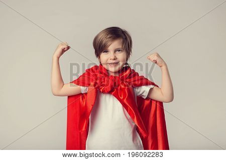 Cute Superwoman Kid In Red Cape Shows Her Muscle