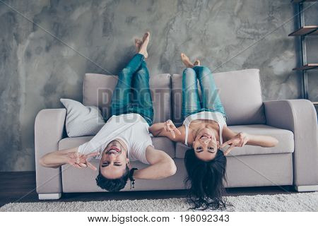 Go Crazy Together! Relaxing Upside Down Is Fun. Cheerful Brother And Sister Are Lying On The Beige S