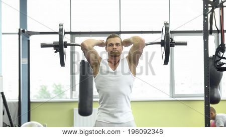 Muscular Man On Strength Training In The Gym. Athlete Makes Triceps Exercise With A Barbell