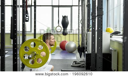 Strength Training In The Gym. Guy Doing Squats With A Barbell. Bodybuilder Doing Exercise With Barbe