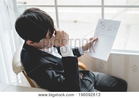 A stressed out business man holds his head in despair as he fears that he will have to file for bankruptcy or go into liquidation