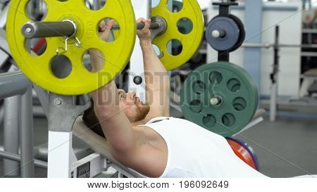 Young Fit Sportsman Doing Barbell Bench Pressing While Exercising At Fitness Club. Muscular Man Exer