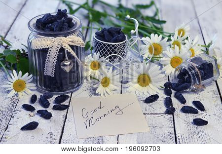 Note with text good morning, flowers and vintage jars with ripe honey berry. Beautiful summer vintage background, vegetarian and vegan concept, rural still life with berry and flowers