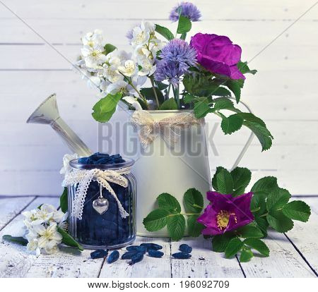Vintage jar with honey berry and watering can with wild flowers. Beautiful summer vintage background, vegetarian and vegan concept, rural still life with berry and flowers