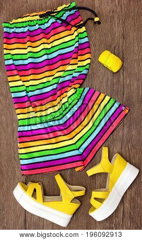 Multicolored striped sleeveless romper, yellow wedge sandals and wide bracelet. Women's summer fashion. Trendy outfit