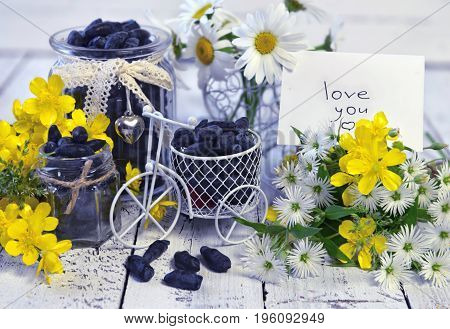 Bunch with wildflowers, blue berry in cute jars and small bicycle. Beautiful summer vintage background, vegetarian and vegan concept, rural still life with berry and flowers