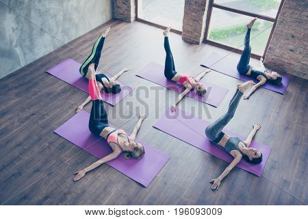 Left-right! Topview Of Spinal Twist, Five Young Sporty Women Are Doing In Modern Studio, Lying On Pu
