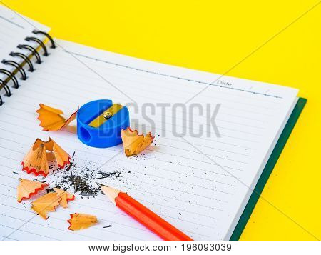 Office accessories including note book red pencil and blue sharpener on yellow background. Education and business concept.
