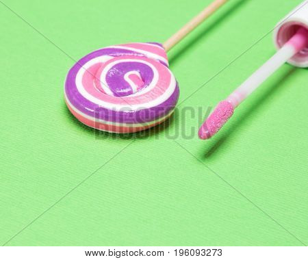 Close up of pink lip gloss with lollipop on green textured background. Shallow depth of field, copy space
