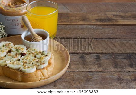 Banana peanut butter toast sandwich on wood plate with honey. Homemade open sandwich spread with peanut butter on top with banana slice and granola. Delicious healthy sandwich toast for breakfast or lunch served with fresh orange juice.