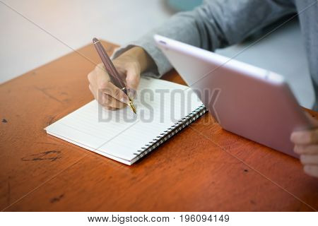 Beautiful Asian Businesswoman Is Taking Notes On Her Notebook While Using The Tablet In Her Office.