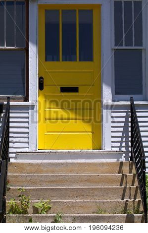 A yellow door on a house sits in the sun.