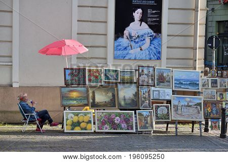VILNIUS LITHUANIA - JULY 18 2017: Street artists sell paintings to the tourists on the street market in Old Town of Vilnius Lithuania. Vilnius is the capital of Lithuania and its largest city.