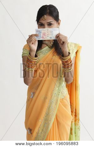 indian woman in saree holding Singapore cash notes