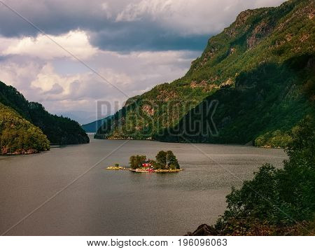 View of the Northern nature - dramatic sky over mountains and a small island among water of a Norwegian fjord.