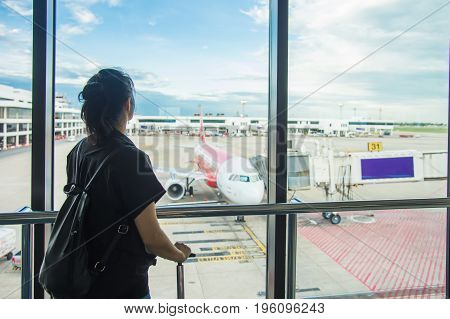 Woman waiting for a flight at the airport; window airport.Young woman in the airport looking through the window at planes