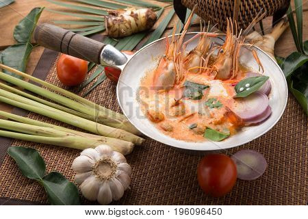 Tom yam kong or Tom yum Tom yam is a spicy clear soup typical in Thailand Cuisine. Tom yam kong on wooden table. Thai food.