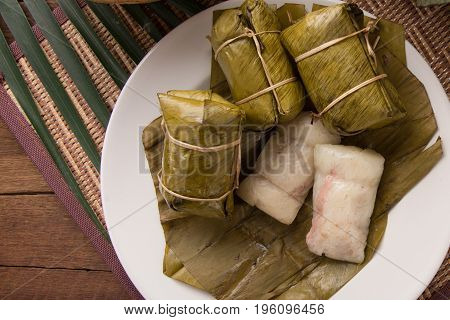 khao tom mad Thai food style dessert made from banana and glutinous rice wrap with banana leaf on wooden table