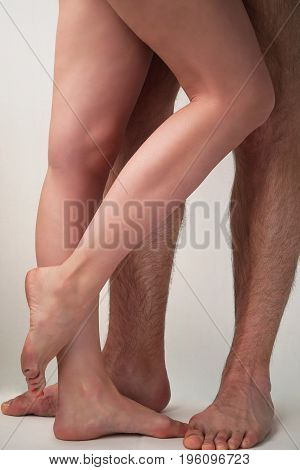Smooth female and hairy male feet on a light background. Sexual overtones.