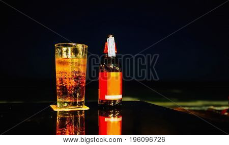 Bottle and grass of beer on the table at the beach during night time.