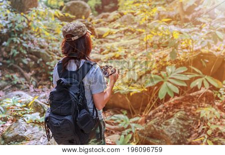 Girl with backpack and camera on trekking trip standing alone in the trail enjoying taking photo over the sunlight.