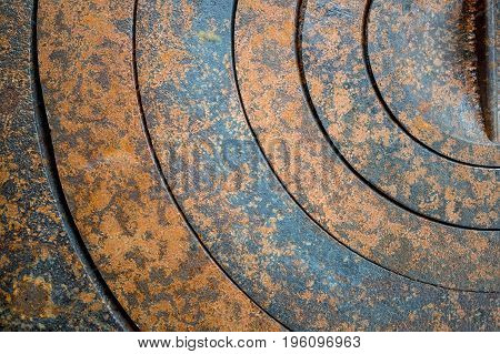 abstract metal background with geometric holes in a circle and texture rust orange-brown with spots. The horizontal frame.