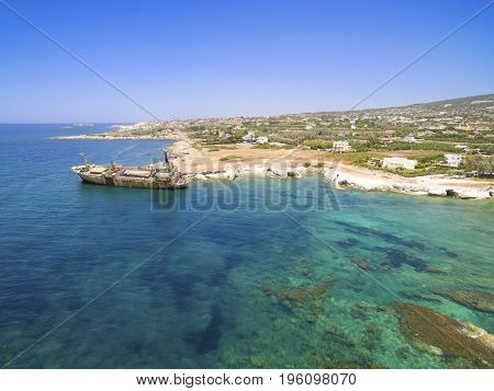 Aerial view of the abandoned ship wreck in Pegeia Paphos Cyprus. The rusty shipwreck is stranded on the Peyia rocks at the kantarkastoi sea caves near Coral Bay in Pafos standing at an angle near the shore.
