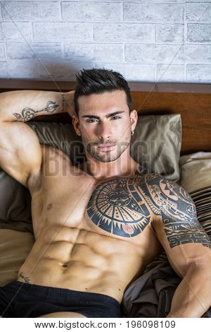 Shirtless sexy muscular male model lying alone on his bed in his bedroom, looking at camera with a seductive attitude