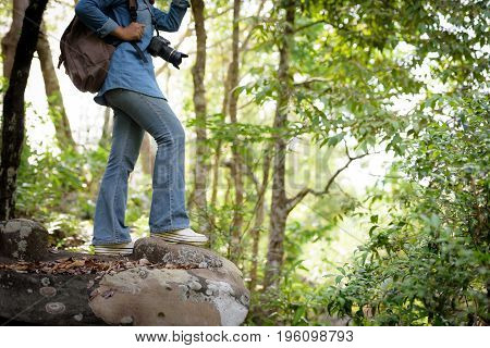 Beautiful Asian girl tourist stands on a rock to photograph nature with a digital camera DSLR in the jungle on a high mountain. Holiday Travel Concept.