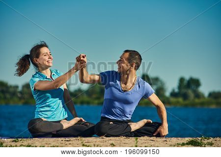 Two young people practicing yoga and sitting in the lotus position