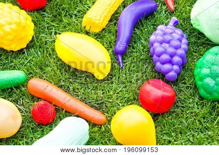 Plastic toy fruits and vegetables on green fresh grass