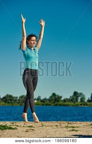 Sporty young woman doing yoga exercises on the riverside