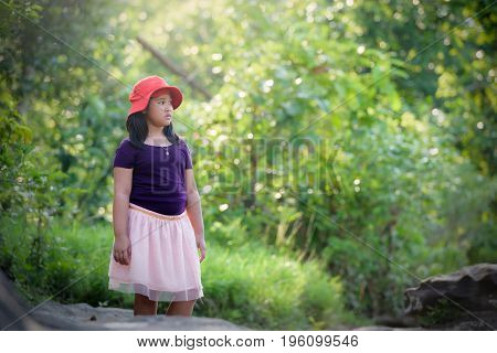 The girl is standing on a rock with a waterfall in a rain forest on a mountain.
