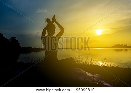 Silhouette Beautiful Women Yoga In Nature On The Rock And River Over Sunset Background.
