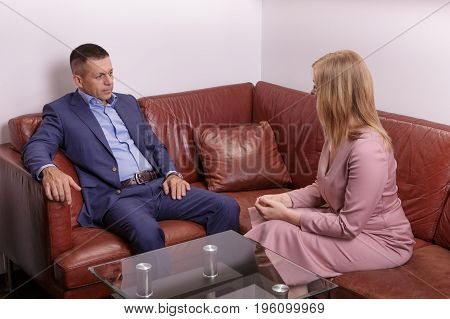 businessman sitting on leather sofa at office listening to talking businesswoman.
