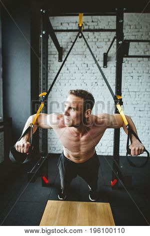 Young handsome man in sportswear exercising at gym on trx